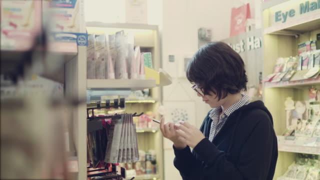 Aziatische jonge meisje selecteren het item op de planken in de winkel