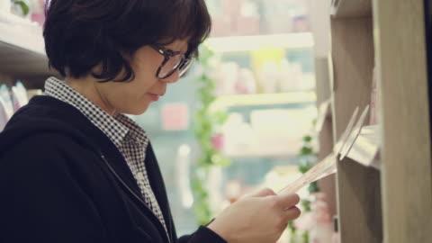 asiatisk ung flicka väljer artikeln på hyllorna i butiken - etikett bildbanksvideor och videomaterial från bakom kulisserna