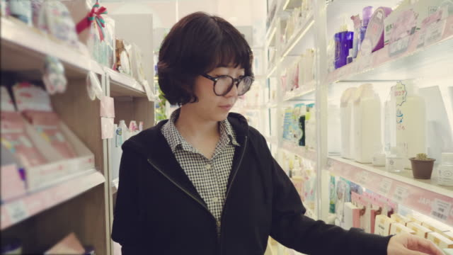 asian young girl selects the item on the shelves in the store - for sale stock videos & royalty-free footage