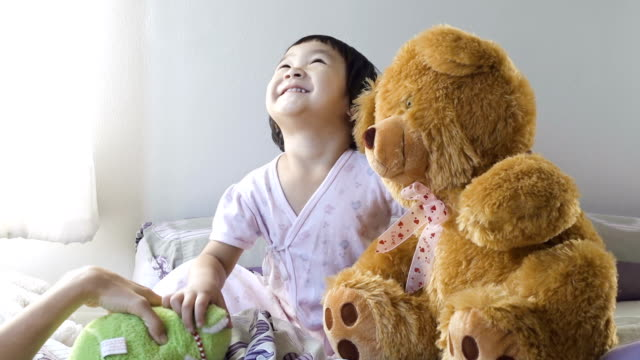 Asian Young Girl With Teddy Bear On Bed