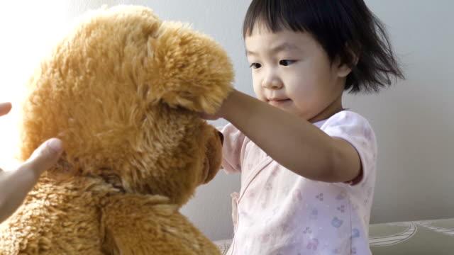 アジアの少女はベッドの上のテディベア - ぬいぐるみ点の映像素材/bロール