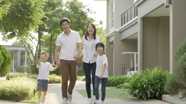 asian young lycklig familj av fyra gå tillsammans utomhus. föräldrar med son och dotter ser glada ut och ler. lycka och harmoni i familjelivet. - gå tillsammans bildbanksvideor och videomaterial från bakom kulisserna