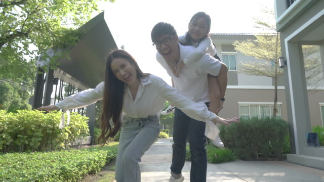 asian young happy family of three having fun together outdoor. pretty little daughter on her father back. parents and girl look happy and smile. happiness and harmony in family life. family fun outside home. - two parents stock videos & royalty-free footage
