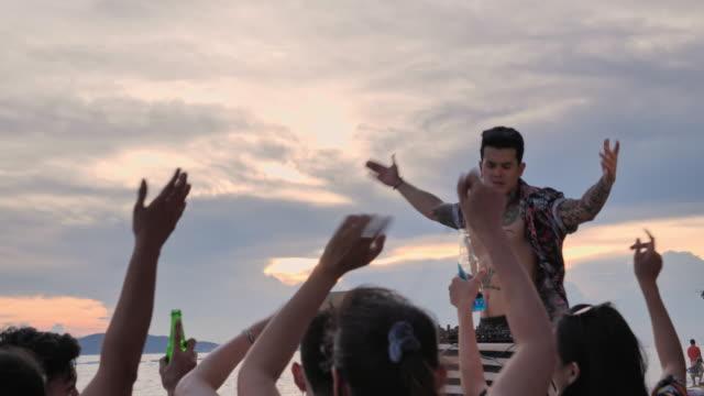 vídeos de stock, filmes e b-roll de homem novo asiático dj que joga a música em uma silhueta da plataforma giratória na praia, os jovens dançam e bebem a cerveja em um partido na praia, dj jogador novo asiático festa de plataforma giratória na praia. - dançar em discoteca