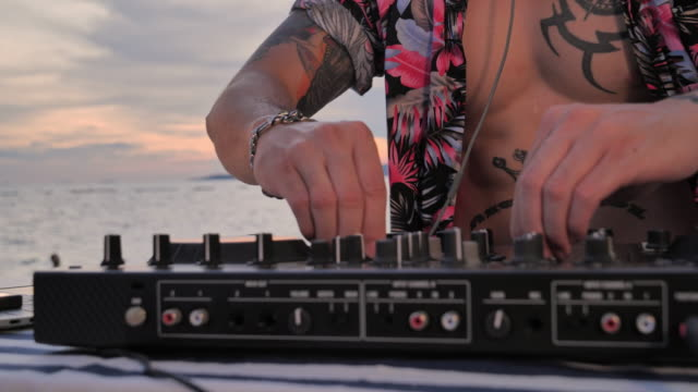 asian young man dj playing music on a turntable silhouette at the beach. - dj stock videos & royalty-free footage