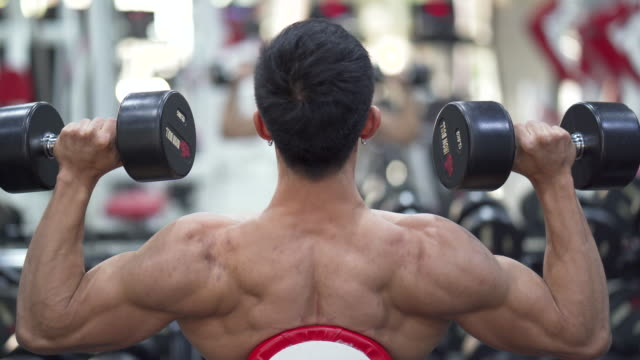 asian young man doing exercises in gym for arms and shoulder back view. - sistema cardiovascolare video stock e b–roll