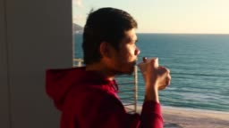 asian young man drink a coffee with beach view