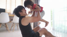 Asian young man exercising with his son at home.
