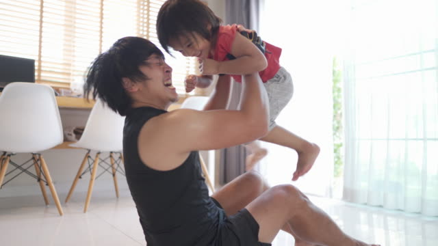 asian young man exercising with his son at home. - active lifestyle stock videos & royalty-free footage