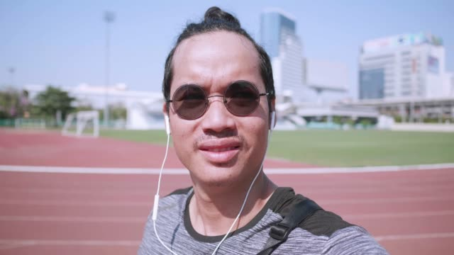 asian young man listen to music and take a walk warm up lab on track before run. - runner bean stock videos and b-roll footage