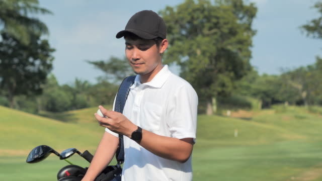 asian young man playing golf walking along fairway carrying golf bag.success, lifestyle, confidence, leadership, power, skill, strength concept.sports cinemagraphs.personal trainer.4k sports - golfer stock videos & royalty-free footage