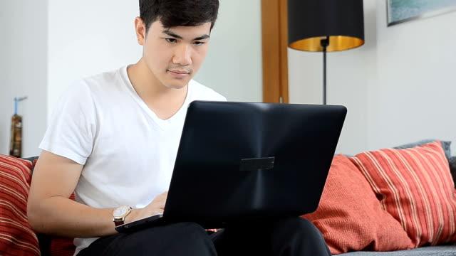 Asiáticos jovem relaxante no sofá com o portátil