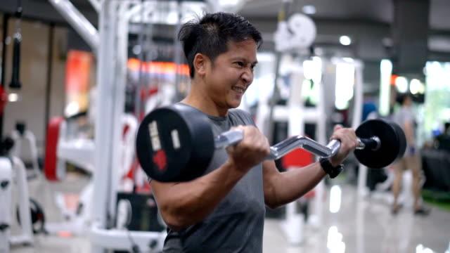 SLO MO のアジア系の若い男、ジム機器のトレーニングです。