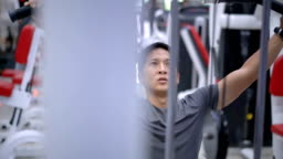 SLO MO Asian young man training on gym equipment.
