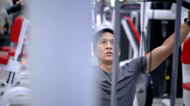 slo mo asian young man training on gym equipment. - weight training stock videos and b-roll footage
