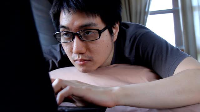 vídeos de stock e filmes b-roll de asian young man wake up and using laptop computer on bed - edredão