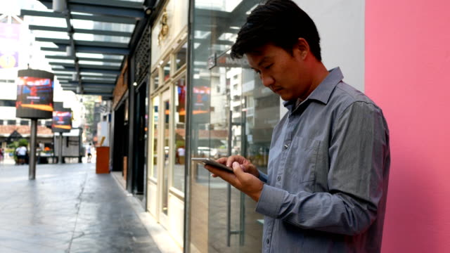 asian young man with mobile phone - holing stock videos & royalty-free footage
