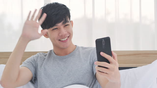 asian young men age 30 yearold on video conference for video call at home with friend or relative during social distancing using by smartphone.social teleconferencing concept. - health technology stock videos & royalty-free footage