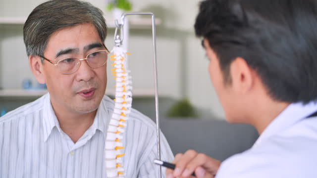 vídeos de stock e filmes b-roll de asian young men doctor explaning anatomical spine to senior men age 54 yearold patient in clinic.male medical staff concept. - human spine