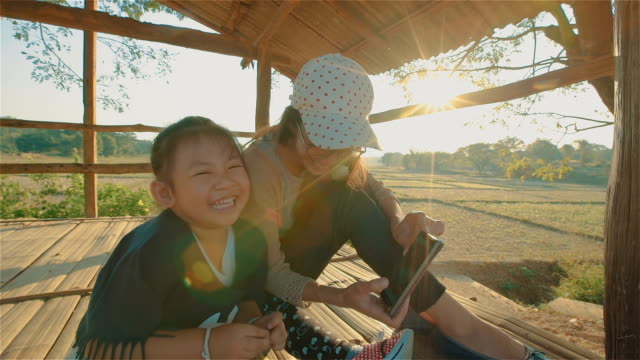 Asian young Mother And Daughter Child using smartphone outdoors