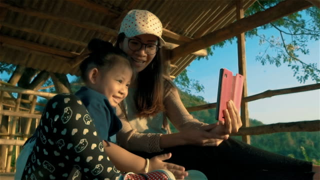 Asian young Mother and daughter sitting in nature while making video call on smart phone outdoors