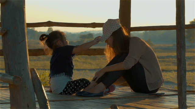 Asian young mother and her Daughter Playing in the hut on autumn field together