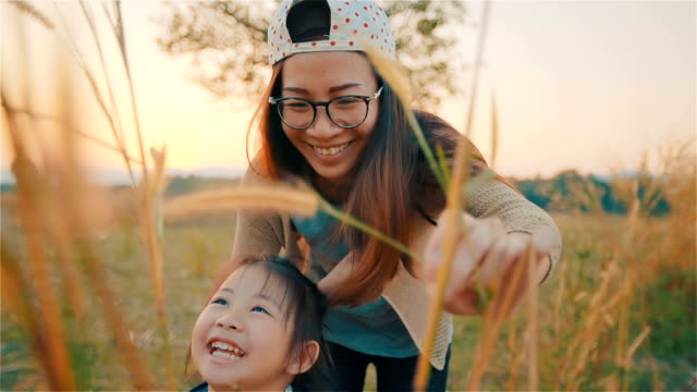 Asian young mother and her Daughter Playing on autumn field together