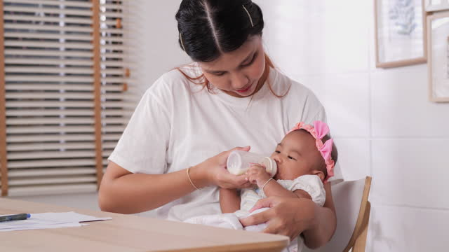 asian young mother feeding her baby at home. - milk bottle stock videos & royalty-free footage