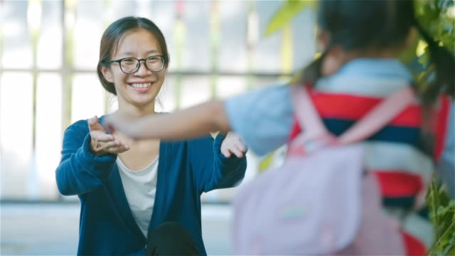 Asian Young mother greeting her daughter after school at house