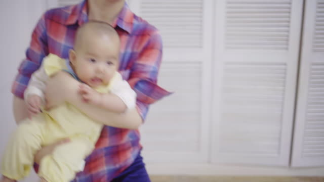vidéos et rushes de asian young mother holding 6 months baby girl spinning - 6 11 mois