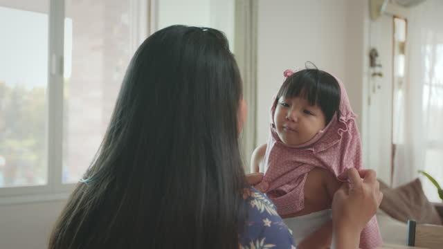 vidéos et rushes de jeune mère asiatique mettant sur la chemise à sa fille à la table. fille asiatique mignonne d'enfant en bas âge jouant avec sa mère tout en portant la chemise. - robe
