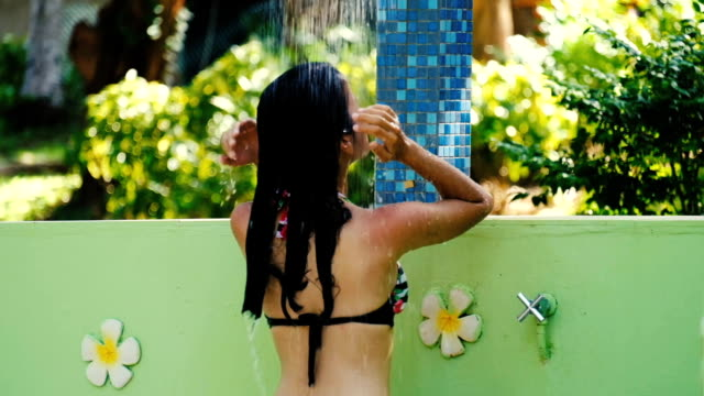 Asian Young slim woman enjoying a refreshing shower in a tropical garden. Slow motion.