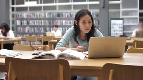 stockvideo's en b-roll-footage met aziatische jonge student vrouw in de bibliotheek lezen van boeken en aantekeningen maken - study