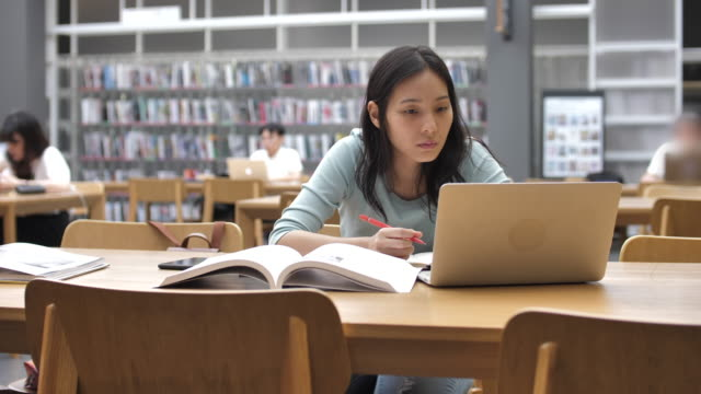 asian young student woman at the library reading books and taking notes - university student stock videos & royalty-free footage