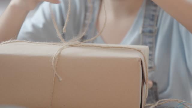 手作りのアイテムケアパッケージを作るアジアの若いティーンエイジャーの女の子。ガートボックスを梱包かわいい女の子は遠くから彼女の家族や友人に送信する準備をします。 - つつむ点の映像素材/bロール