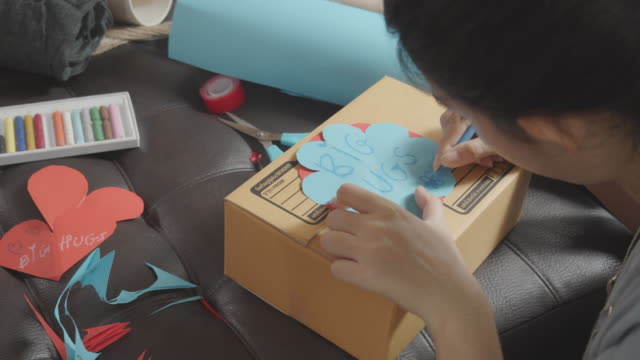 cu: asian young teenager girl making handmade items care package. cute girl packing a girt box prepare to sending to her family or friends from distance. - home made stock videos & royalty-free footage