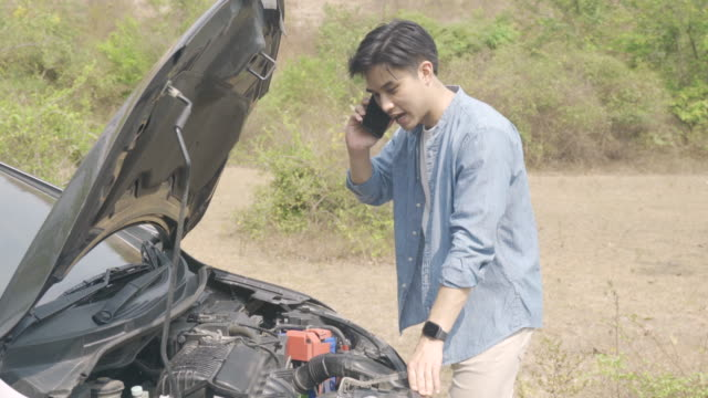 asian young unhappy man talking on a cell phone  in front of the open hood  broken down car on country road phoning. broken car on the road in during journey. - bonnet stock videos & royalty-free footage