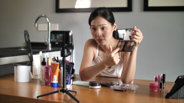 vidéos et rushes de jeune femme asiatique blogueur enregistrant la vidéo de vlog avec le cosmétique de maquillage à la maison - influenceur