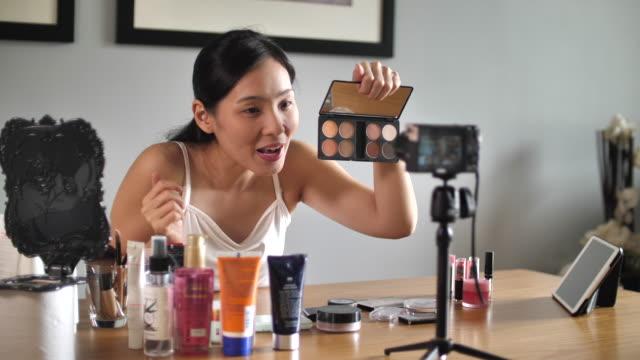 アジアの若い女性ブロガーは、自宅でメイクアップ化粧品でvlogビデオを記録 - 趣味点の映像素材/bロール