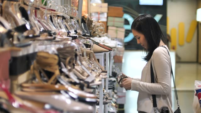 asian young woman choosing shoes at store - dress shoe stock videos & royalty-free footage