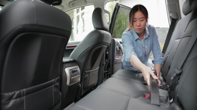 asiatica giovane donna pulizia auto con un vuoto - clean video stock e b–roll