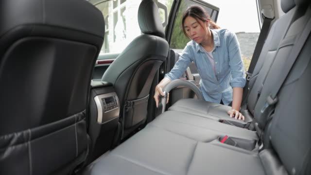 vídeos de stock, filmes e b-roll de asiático jovem limpando carro com um vácuo - só uma mulher de idade mediana