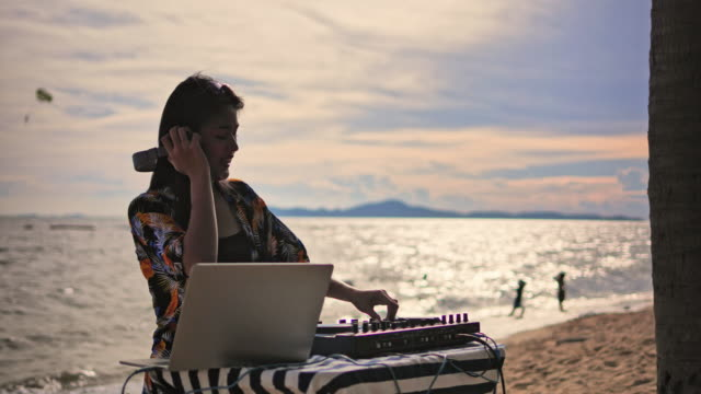 asian young woman dj playing music on a turntable silhouette at the beach. - deck stock videos & royalty-free footage
