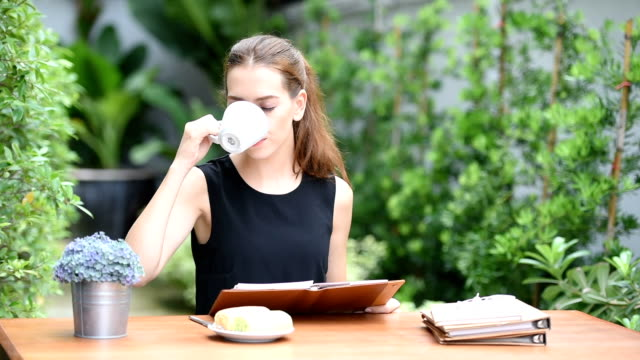 asian young woman drink a cup of coffee on table in the garden - coffee drink stock videos & royalty-free footage