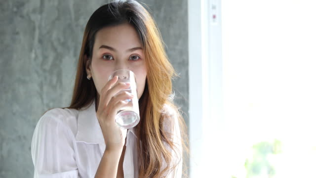 Asian Young woman drinking glass of water in bed at morning