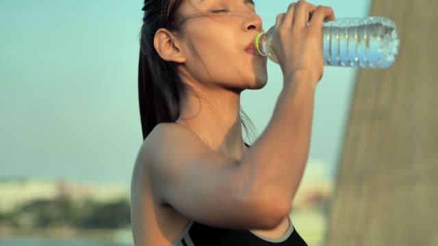 高強度のトレーニングの後に水分補給のために水を飲むアジアの若い女性。ライフスタイル,成功,パワー,健康,リーダーシップ,スポーツにおける女性,スポーツ準備 - のみ点の映像素材/bロール