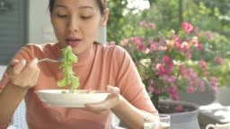Asian young woman eating fresh salad