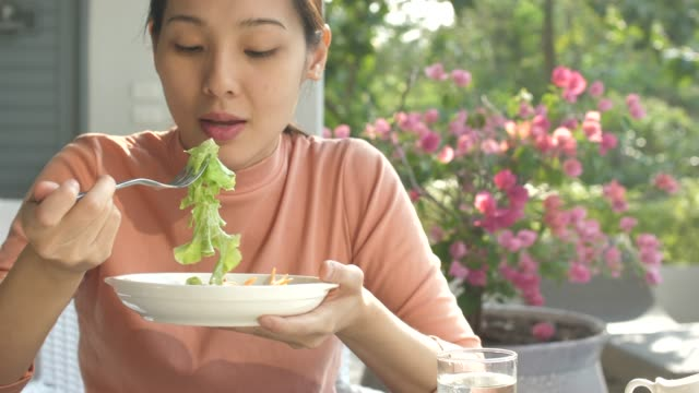 asian young woman eating fresh salad - young women stock videos & royalty-free footage