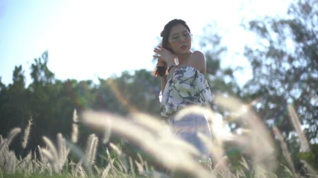 stockvideo's en b-roll-footage met aziatische jonge vrouw die aard en zonlicht geniet. - menselijke arm