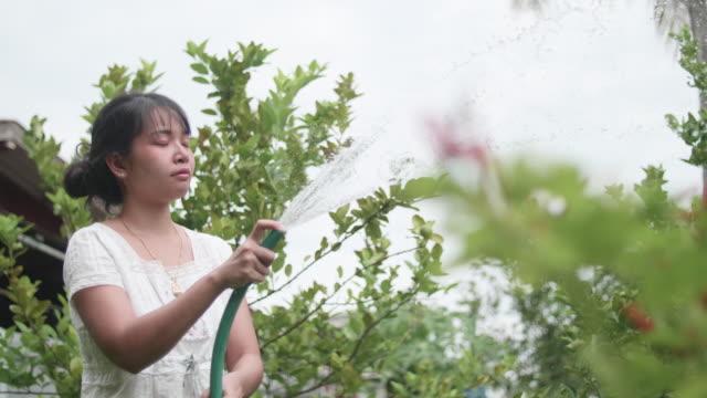 裏庭のアジア系の若い女性の園芸の花。 - 園芸学点の映像素材/bロール